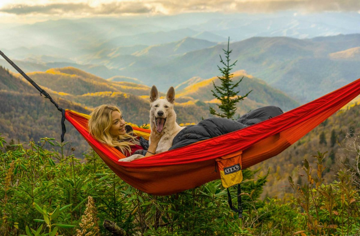 woman in hammock with dog